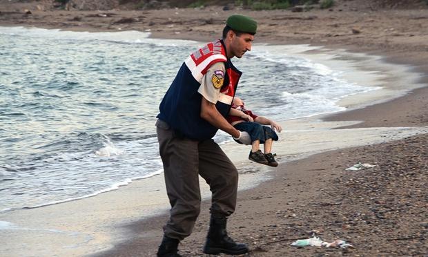 Policía levanta el cuerpo del niño sirio, ahogado en la costa de Turquía en su intento de llegar a Europa. Foto: The Guardian