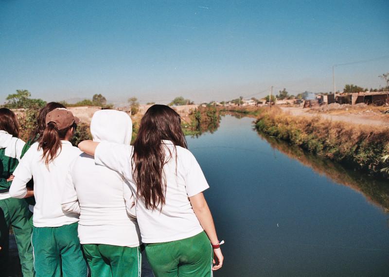 Un grupo de jóvenes observan un canal contaminado que desemboca en el río Santiago. Foto: César Octavio Huerta
